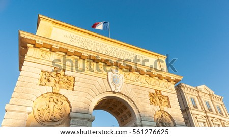 French flag flutters against blue sky sun casts golden hue on Arch of Triumph at entrance or Porte du Peyrou   situated at  eastern end of  Jardin de Peyrou, a park near center of the city.