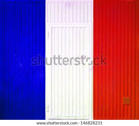 French flag on the background of old locked doors. - stock photo