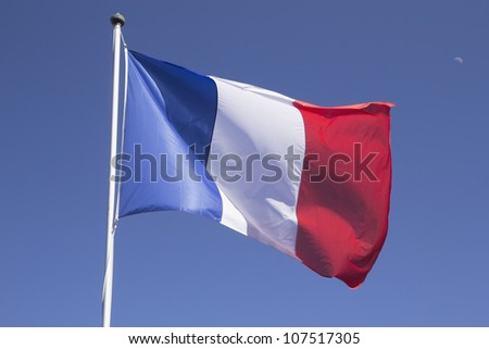 French flag on the mast. Blue sky with the moon in the background. - stock photo