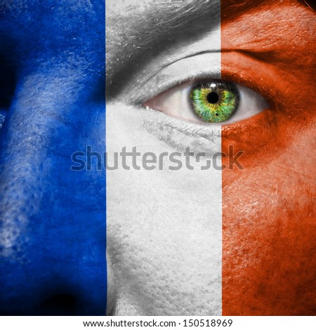 French flag painted on mans face to support his country France - stock photo