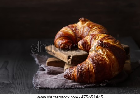 French food for breakfast. Fresh baked croissants. Dark wood background