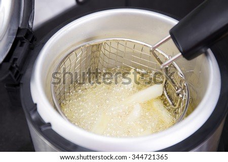 French fried in hot vegetable oil on electronic pot - stock photo