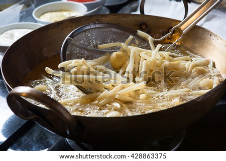 French fried potatoes frying in boiling oil, Cooking  - stock photo