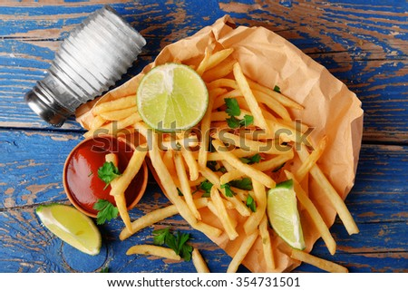 French fried potatoes on craft paper on cutting board - stock photo