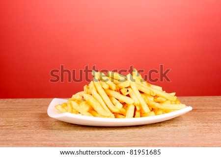 French fries and a plate on a red background - stock photo