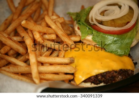 French Fries and Cheese Burger in a restaurant. Shot at a shallow depth of field focus on the French fries .  - stock photo