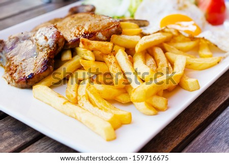French fries and fried meat, fried egg. - stock photo