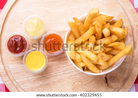 french fries and sauses on wood tray