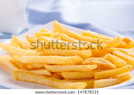 French fries in a plate against a large tablecloth - stock photo