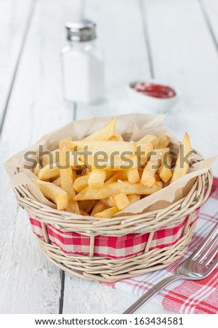 French fries in a wicker basket on white wood table with salt shaker and ketchup - rural bar or fast food menu - stock photo