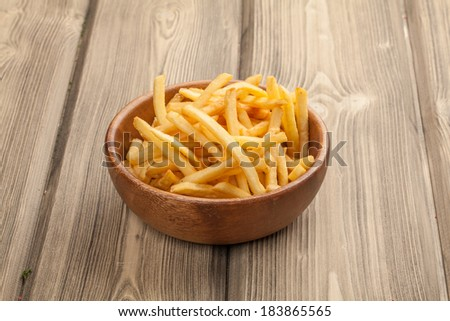 French fries in a wooden bowl, on a wooden background.  - stock photo