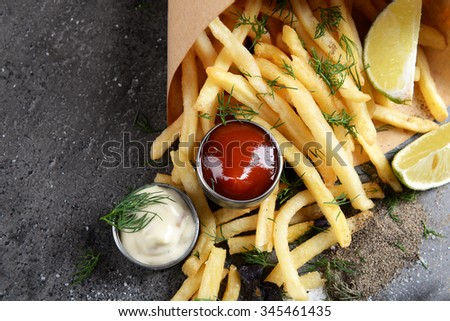 French fries in bag with sauce, lime and spice on table - stock photo
