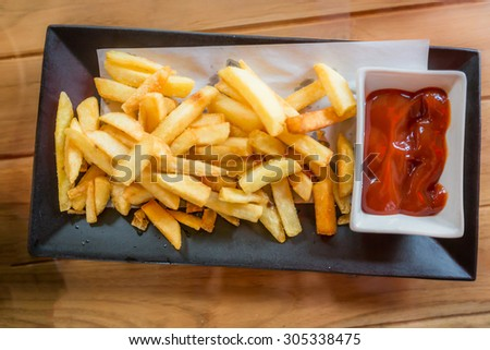 French fries in black plate serve with tomato and chilli sauce. - stock photo