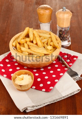 French fries in bowl on wooden table close-up - stock photo