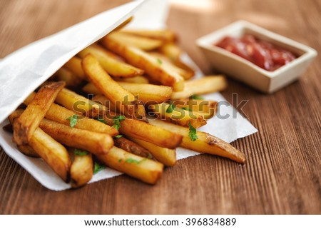 french fries in paper bag and red sauce. selective focus