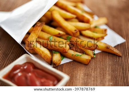 french fries in paper bag and red sauce. selective focus - stock photo