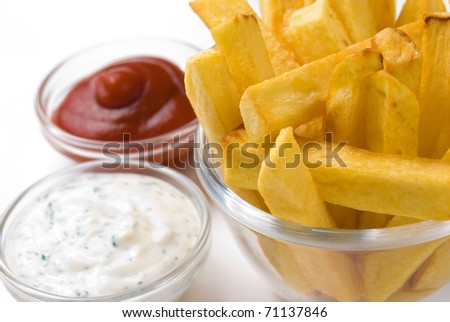 French fries in the glass bowl with dipping sauces aside over white background - stock photo