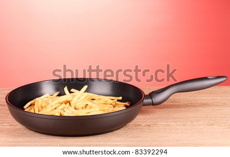 French fries in the pan on a red background
