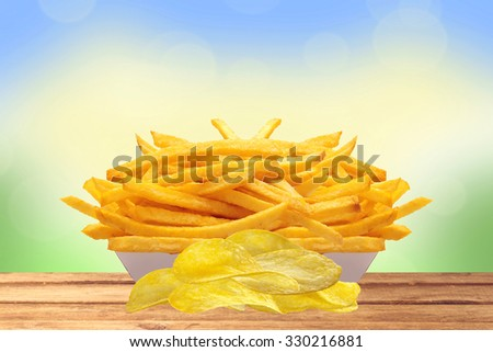 French fries in white box and chips on wooden table over nature background