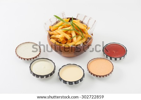 French fries in wood bowl garnished with Japanese bamboo leaves with 5 sauce tartar sauce, wasabi mayo sauce, mayonnaise, thousand island sauce, and ketchup - stock photo