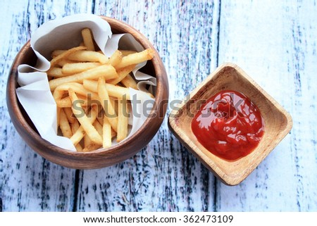 french fries in wooden bowl with white parchment paper around them with a small bowl of ketchup inside on a wooden background/fries and ketchup/fried goodness  - stock photo