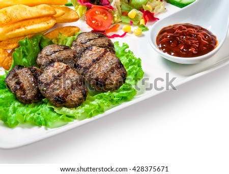 French fries, meatballs on the lettuce, vegetables and barbecue sauce in a bowl on white background