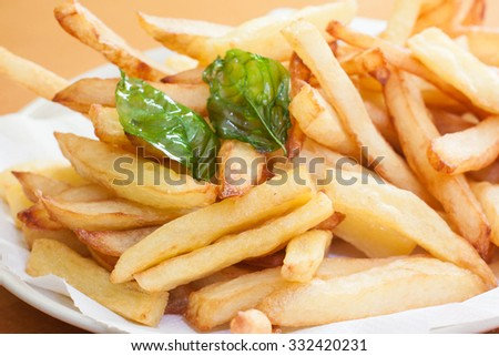 french fries on plate with deep fried basil leave - stock photo