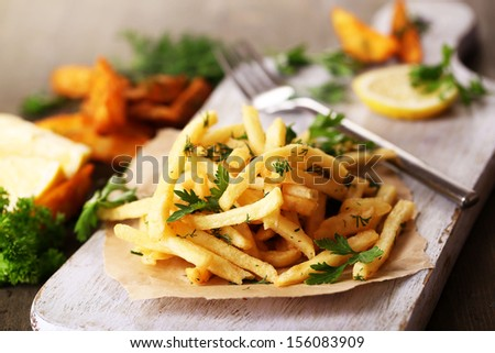French fries on tracing paper on board on wooden table - stock photo