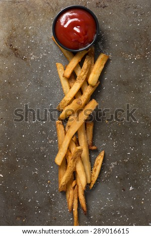 french fries, pink himalayan sea salt and ketchup styled in a baking pan, top view, close up, vertical - stock photo