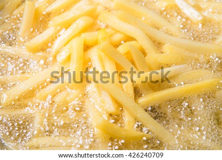 French fries potatoes frying in boiling oil. - stock photo