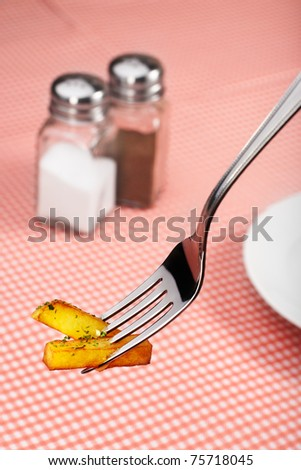 French fries potatoes on fork. Red background - stock photo