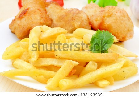 French fries with fried chicken on a white plate