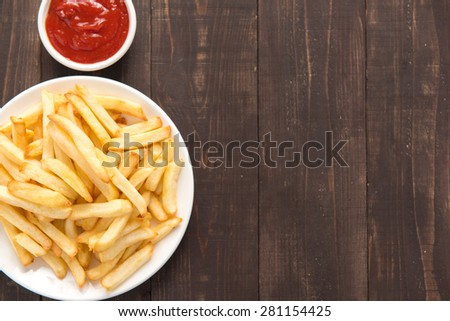 French fries with ketchup on wooden background. - stock photo