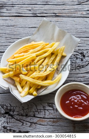 French fries with ketchup on wooden table - stock photo