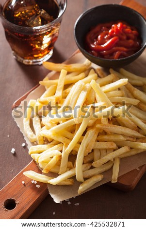 french fries with ketchup over rustic background - stock photo