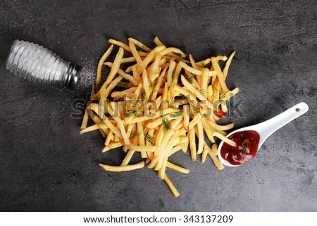 french fries with ketchup, salt and dill on table - stock photo