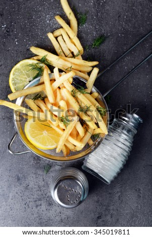 French fries with lemon and salt in sieve on table - stock photo