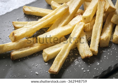 French fries with sea salt, on black slate.  Side view. - stock photo