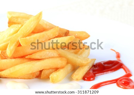 French fries with tomato sauce and mayonnaise on white background. - stock photo