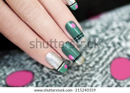 French green manicure with stripes and pink dots graphic background. - stock photo