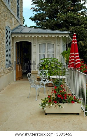French guest house terrace with chairs and table - stock photo