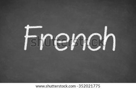 French lesson on blackboard or chalkboard. written in white chalk - stock photo