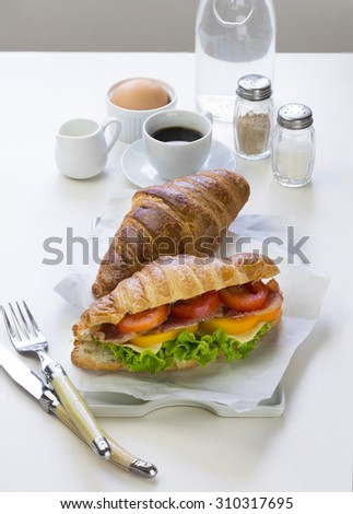 French loaf Cheese and ham sandwich served with espresso coffee and on white table top. - stock photo