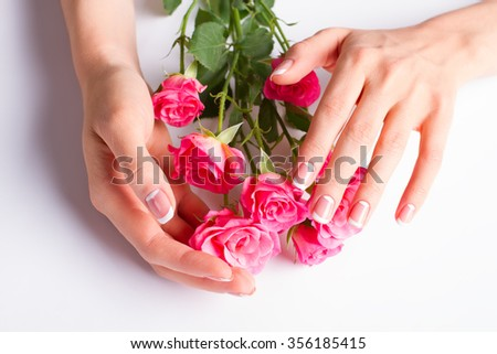 French lunar manicure with bouquet of pink roses close-up.