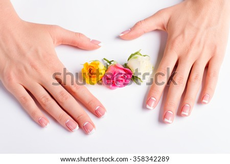 French lunar manicure with buds of colorful roses close-up.