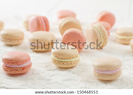 French macarons (pronounced macaroon, a popular buttercream filled meringue type cookie or biscuit) on white wood table with lace over. In soft pink and white hues with bright backlight - stock photo