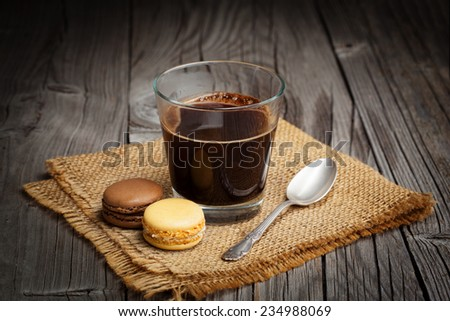 French macaroons and cup of coffee on a dark rustic wooden background, selective focus - stock photo