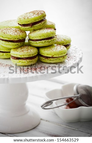 French macaroons in green with cocoa powder - stock photo