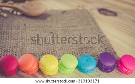 French macaroons on sack with wood background on filter color