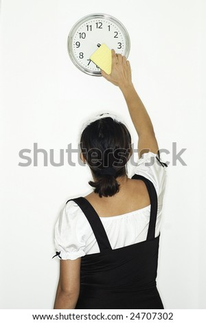 French Maid cleaning wall clock - stock photo